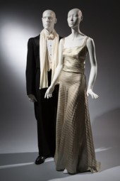 Elegance in the Age of Crisis: Fashions of the 1930's Wood Carlson Co., tailcoat, black wool, 1935, USA, gift of Kay Kerr Uebel, 89.65.9 / Gown, metallic, silk, circa 1935, USA, gift of Mrs. Jessie L. Hill, 93.71.12